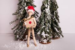 Jointed mannequin doll holding holiday Christmas present on winter scene. Wooden jointed mannequin figure doll holding wrapped holiday Christmas present on royalty free stock photography