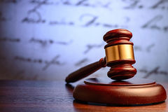 Wooden judge or auctioneers gavel. On a plinth with a defocused background of a hadwritten document conceptual of justice and sentencing royalty free stock photography