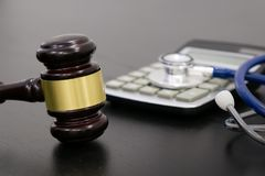 Wooden judge gavel, calculator and stethoscope on table. black background, the concept of medical malpractice, a. Wooden judge gavel, calculator and stethoscope Royalty Free Stock Photography