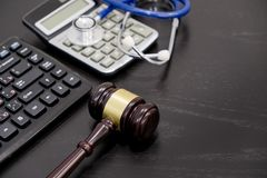 Wooden judge gavel, calculator and stethoscope on table. black background, the concept of medical malpractice, a. Wooden judge gavel, calculator and stethoscope Stock Image