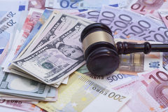 Wooden judge gavel on dollars end euro banknotes Stock Photo
