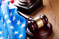 Wooden judge hammer on american flag background stock photos