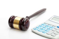 Wooden judge's gavel and calculator next to it Stock Photos