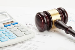 Wooden judge's gavel and calculator over contract - close up studio shot Stock Images