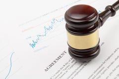 Wooden judge's gavel over agreement document Stock Photos