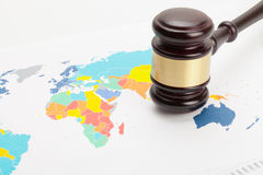 Wooden judge's gavel over colorful world map Royalty Free Stock Photography