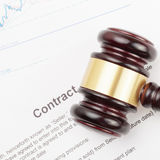 Wooden judge's gavel over contract and financial charts - close up shot Stock Photography