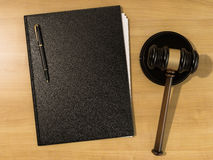 Wooden judges gavel and leather folder on the wooden background Stock Photos