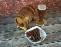 Wooden keg, glass of light beer and a plate with snacks on the table. Close-up stock photography