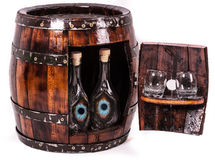 Wooden keg like table. Wooden keg or oak barrel  with two glasses of brandy and bottle of brandy with desperate eyes Royalty Free Stock Photos