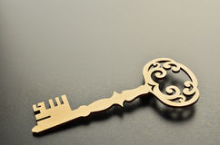 Wooden key on grey background. Wooden key silhouette with shadow on grey chalkboard background, copy space stock images