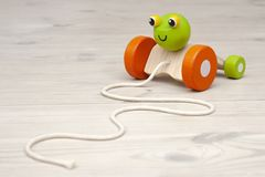 Wooden kids toy on a white wooden floor stock photos