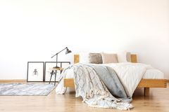 Wooden king-size bed in bedroom. Bedsheets on wooden king-size bed against white wall in spacious bedroom with lamp on a stool royalty free stock photography