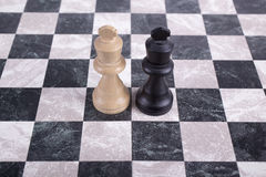 Wooden kings on chessboard. Black and white wooden kings on chessboard Stock Photo