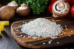 Wooden kitchen board with the rice on it, arounded by vegetables and spices. Wooden kitchen board with the rice on it, arounded by vegetables and spices Stock Photography