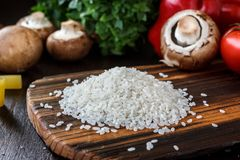Wooden kitchen board with the rice on it, arounded by vegetables and spices. Wooden kitchen board with the rice on it, arounded by vegetables and spices Royalty Free Stock Photos