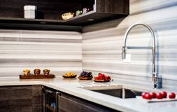Wooden kitchen cabinets with white kitchen granite countertop. Counter concept. White granite counter top with food decoration on it and brown wooden kitchen royalty free stock photography