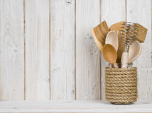 Wooden kitchen cooking utensils in handmade storage pot on shelf.  stock image