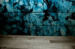 Wooden kitchen counter in front of flower patterned tiles in blue. royalty free stock images