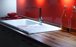 Wooden Kitchen Counter. Modern Stylish Kitchen with Wooden Counter, White Enamel Sink and Modern Silver Faucet Tap Royalty Free Stock Image