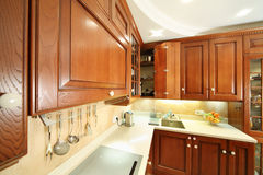 Wooden kitchen. Cupboards, sink and cooker in light clean kitchen Stock Image