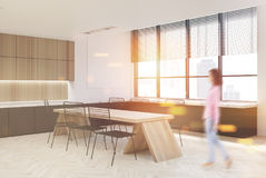 Wooden kitchen interior, dark countertops, girl. Wooden kitchen interior with a white table with chairs, marble countertops and a row of wooden cupboards. A Royalty Free Stock Image