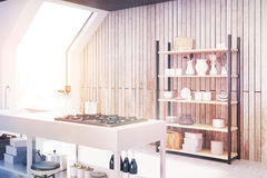 Wooden kitchen interior, side, toned. Side view of an interior of an attic kitchen with wooden walls, a cooker, a sink and a cupboard with dishes and cutting Royalty Free Stock Photo