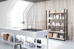 Wooden kitchen interior, side. Side view of an interior of an attic kitchen with wooden walls, a cooker, a sink and a cupboard with dishes and cutting boards. 3d Stock Images