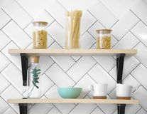 Wooden kitchen shelves with cups and glass Jars. On white wall stock photos