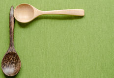 Wooden kitchen spoons on green tablecloth Stock Images