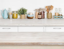 Wooden kitchen table over blurred furniture shelf with food ingredients Royalty Free Stock Photography