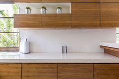 Wooden kitchen units. And white worktop in modern interior stock photography