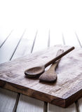 Wooden kitchen utensils on the board. Empty wooden board on the table. Free space for your information Stock Photos