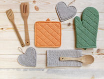 Wooden kitchen utensils,potholder, glove and napkin on wooden t Royalty Free Stock Photography