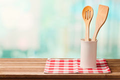 Wooden kitchen utensils on table with tablecloth over blue bokeh background with copy space for product montage Royalty Free Stock Images