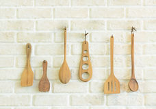 Wooden kitchen utensils on white brick wall Stock Photography