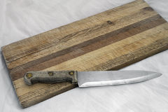 Wooden knife on grainy old fashioned cutting board Royalty Free Stock Image