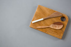 Wooden knife and spoon on chopping board Royalty Free Stock Images