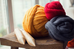 Wooden knitting needles and merino wool balls, lying on wooden s Royalty Free Stock Images