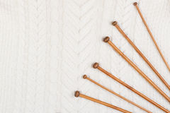 Wooden knitting needles on white knitting wool texture background Royalty Free Stock Photo