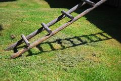 Wooden ladder. On grass in front of a barn, casting a shadow on the ground Royalty Free Stock Photos