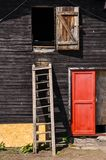 Wooden ladder on a cottage wall with red door Stock Image