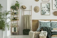Ladder with coverlet. Wooden ladder with coverlet and straw hat standing next to bed in bright room with plants Royalty Free Stock Photos
