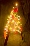The wooden ladder decorated with Christmas lights. The shape of Stock Image