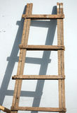 Wooden Ladder and Shadow. Handmade wood ladder resting on a white wall casting a shadow Royalty Free Stock Photography