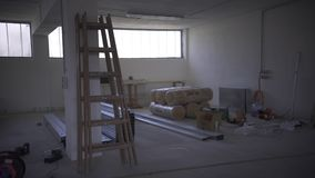 A wooden ladder stands on a construction site in a finished room next to a pillar.  stock footage