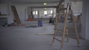 A wooden ladder stands on a construction site in a finished room next to a pillar.  stock video footage