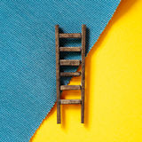 Wooden ladder on yellow and blue background Stock Photo
