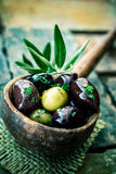 Wooden ladle filled with seasoned olives Stock Image