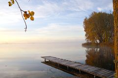 Wooden lake bridge and golden autumn morning mist Royalty Free Stock Photography